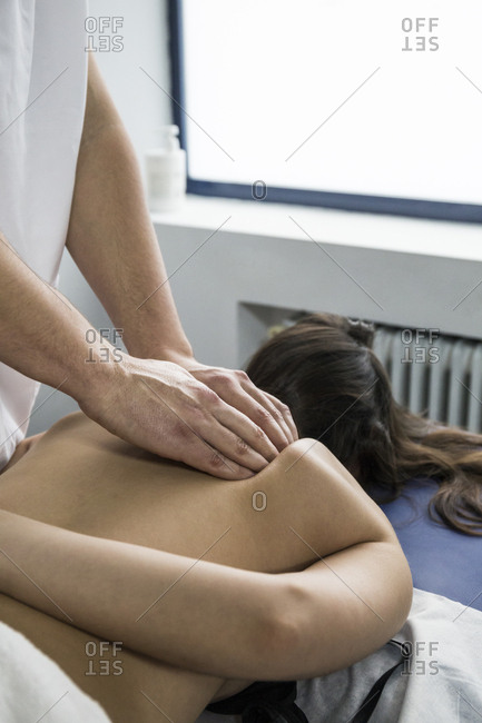 Hands of a physiotherapist massaging near a client's shoulder blade