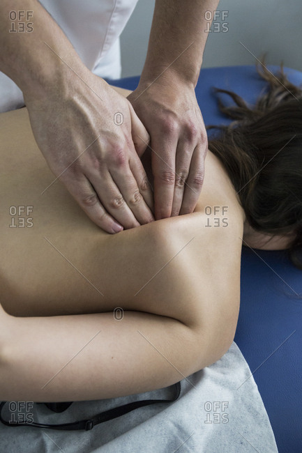 Physiotherapist massaging a patient's shoulder blade in a clinic