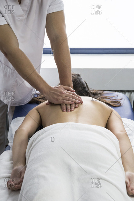 Physiotherapist treating a client's back at a clinic