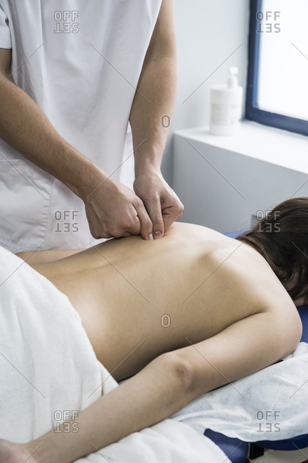 Hands of a physiotherapist massaging the back of a client on a table