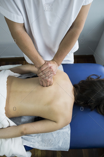 Hands of a physiotherapist kneading the back of a client on a table