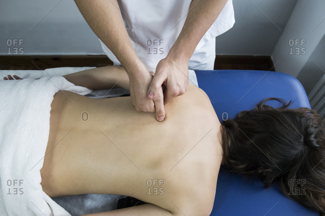 Hands of a physiotherapist massaging the back of a client lying on a table