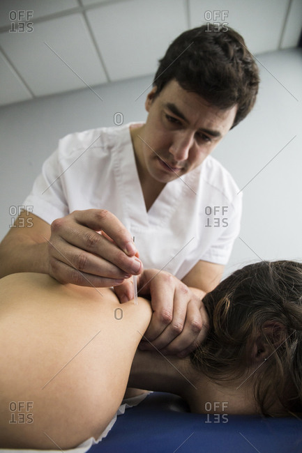 Physiotherapist performing a dry needling procedure on a client's shoulder