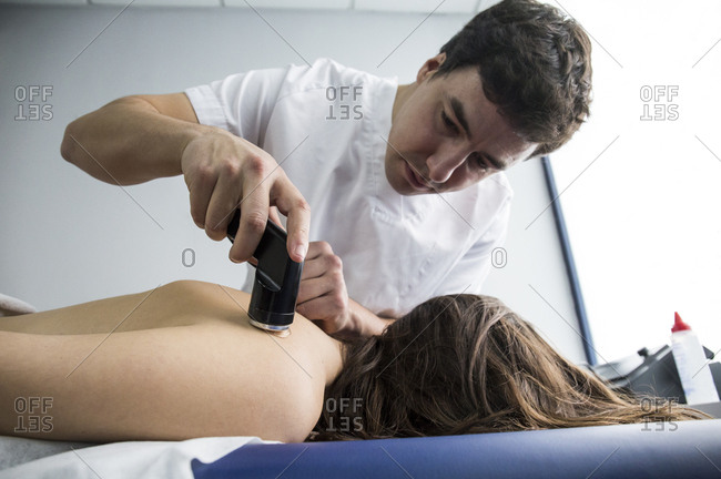Physiotherapist rubbing a client's back with an ultrasound machine