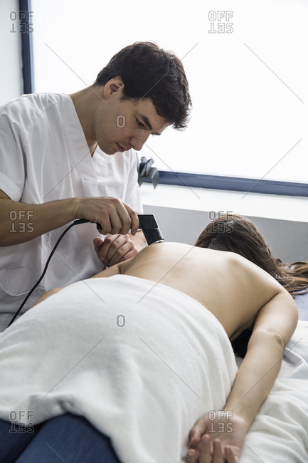 Physiotherapist treating a client's shoulder with an ultrasound machine