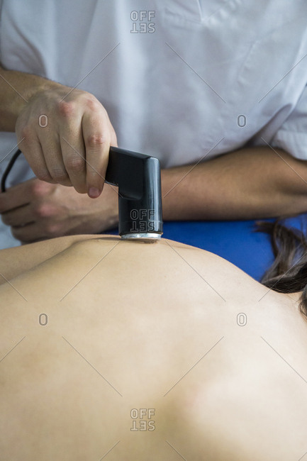 Hands of a physiotherapist treating a client's shoulder with an ultrasound machine
