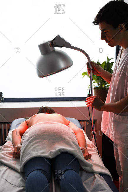 Physiotherapist treating a patient with an infrared lamp