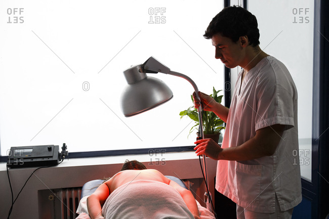Physiotherapist using an infrared lamp to treat a patient