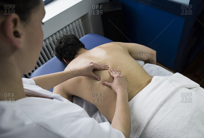 Physiotherapist massaging a male patient's back on a table