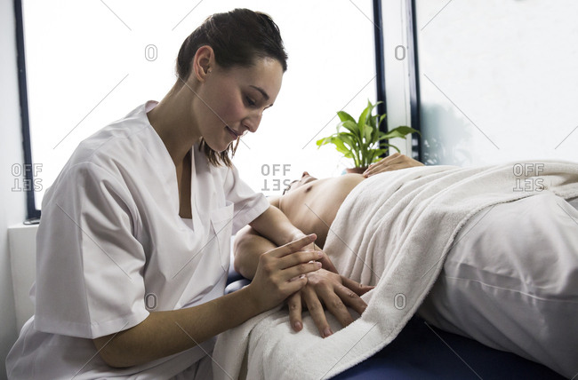 Physiotherapist treating the hand of a patient with a dry needling procedure