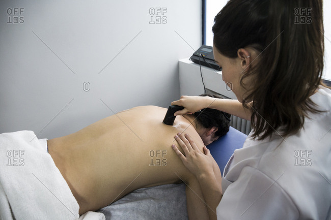 Physiotherapist rubbing a patient's back with an ultrasound machine