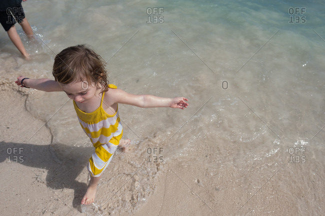 Overhead view of young girl wading in ocean