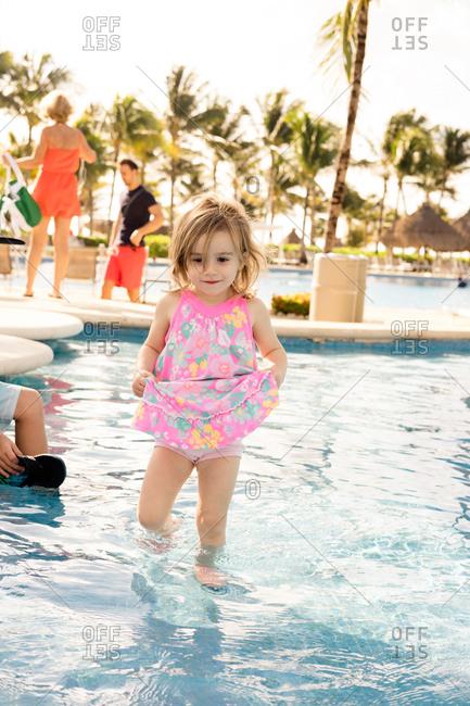 Toddler girl wading in pool