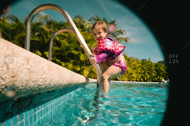 Girl climbing down ladder into pool
