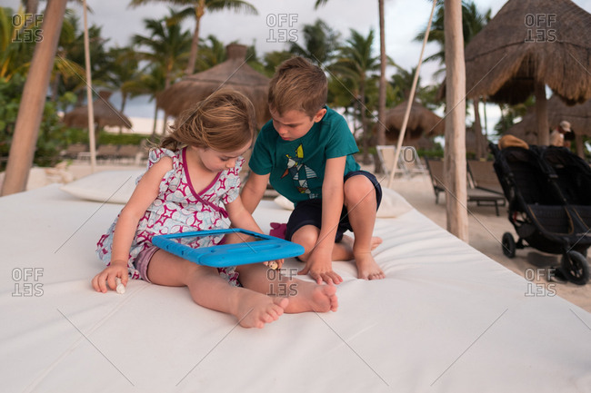 Children using tablet computer on beach lounge chair