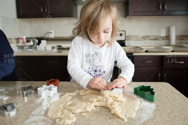 Young girl cutting dough with cookie cutters