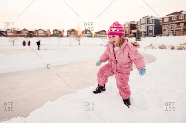 Young girl climbing over snow bank to get to ice