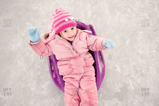 Overhead view of girl in snowsuit lying in sled