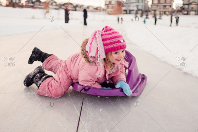 Young girl in snowsuit climbing on sled