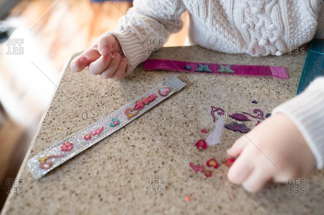 Preschool girl making sticker bracelets