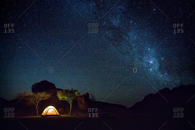 Glowing tent in desert at night with Milky Way visible in sky