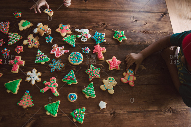 Children with arrangement of decorated Christmas cookies on table