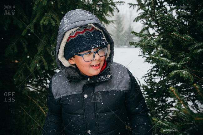 Young boy with glasses amidst pine trees in snowy weather