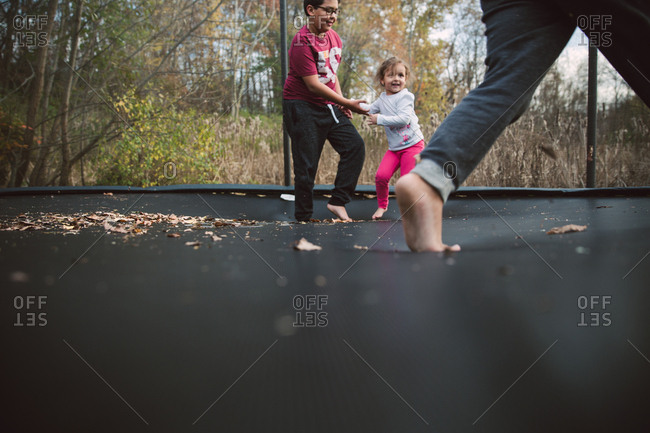 Boy playing with his sister on backyard trampoline