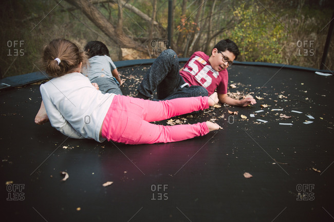 Siblings lying on trampoline