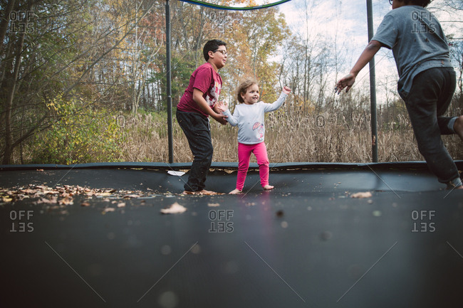 Two boys playing on trampoline with their younger sister
