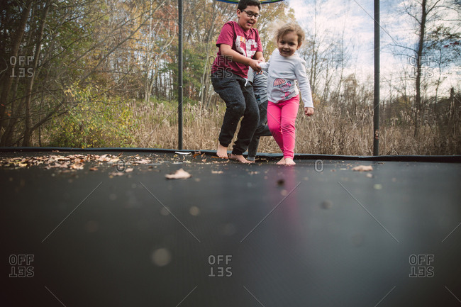 Children playing on backyard trampoline
