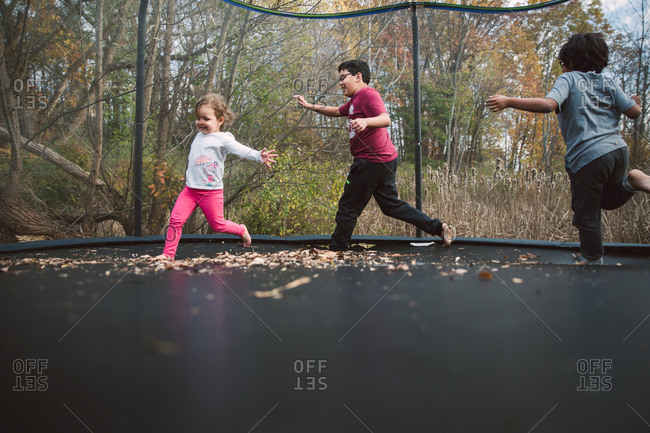 Three kids running on trampoline