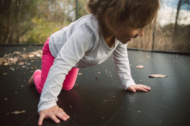 Toddler girl crawling on trampoline
