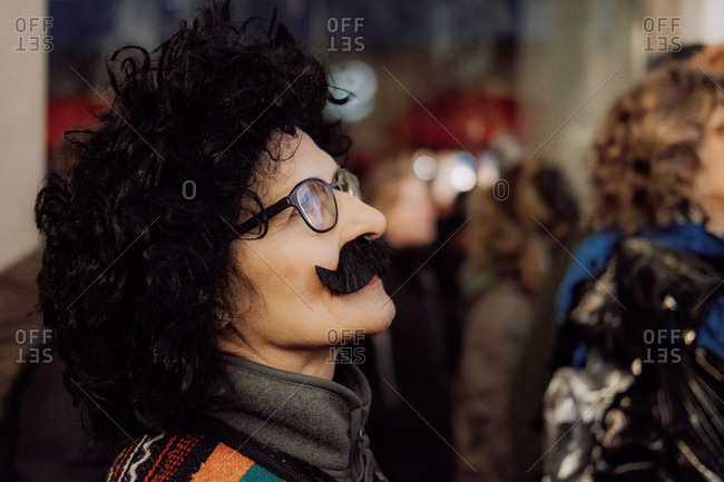 Lucerne, Switzerland - February 25, 2017: Woman watching the Lucerne Carnival Parade dressed in costume with mustache
