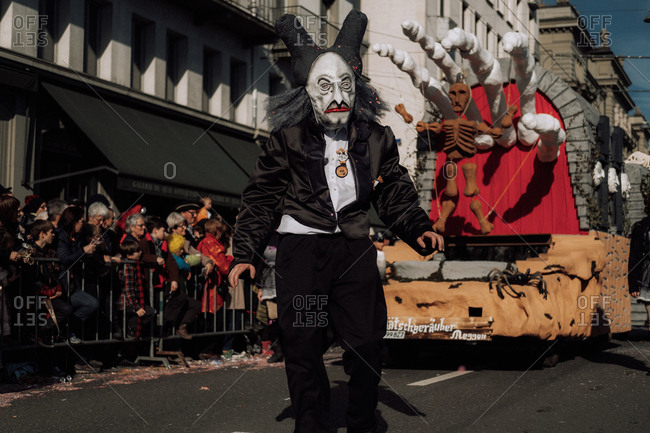 Lucerne, Switzerland - February 25, 2017: Person dressed in scary costume walking by float with skeleton at the Lucerne Carnival Parade