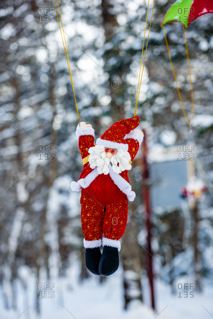 Santa Claus ornament hanging in snowy landscape