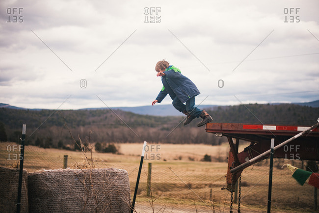Boy leaping from farm equipment