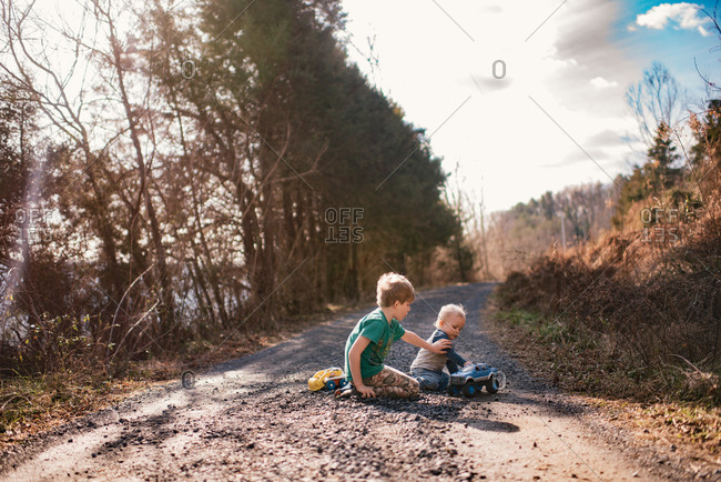 Two boys playing with toy trucks on a dirt road