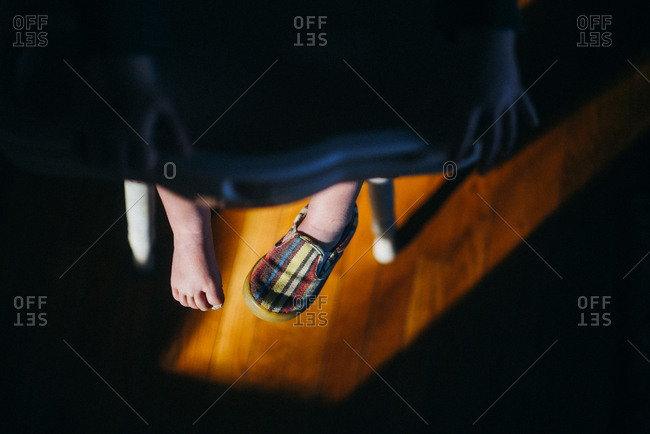 High angle view of toddler's feet hanging from high chair