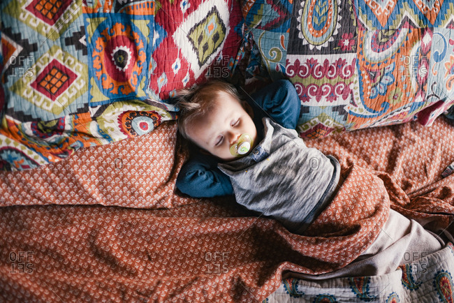 Overhead view of toddler boy sleeping in a bed