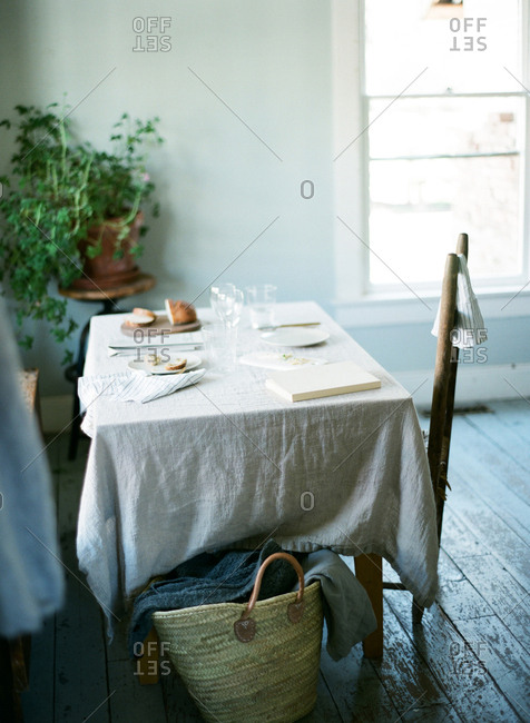 Basket on floor beside table and chairs and white tablecloth