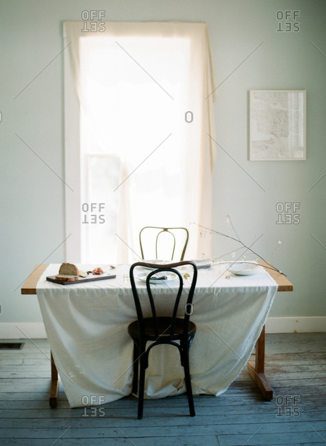 Table with two chairs and white tablecloth