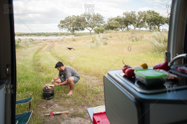 Extremadura, Spain - May 26, 2016: Man starting fire in grill while camping