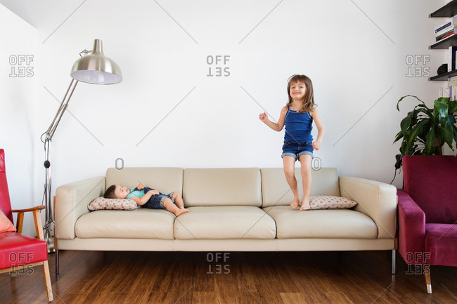 Girl jumping on the couch while toddler sister is lying down