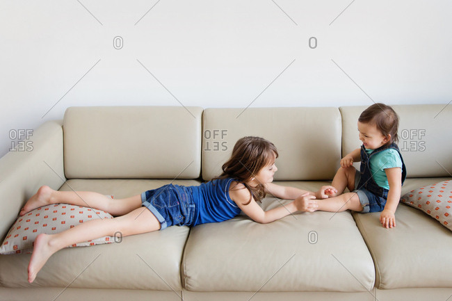 Girl tickling feet of her little sister