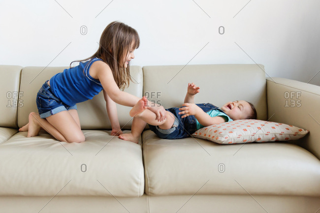 Girl tickling leg of her little sister