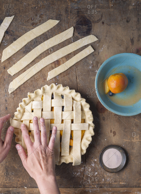 Person finishing making lattice on top of a pie