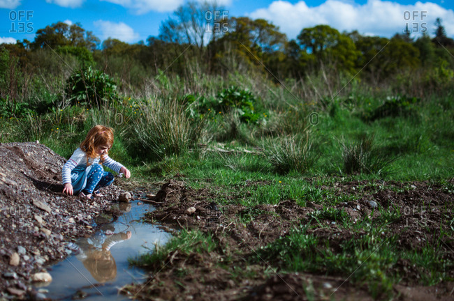 Girl playing at a puddle in a field with reflection