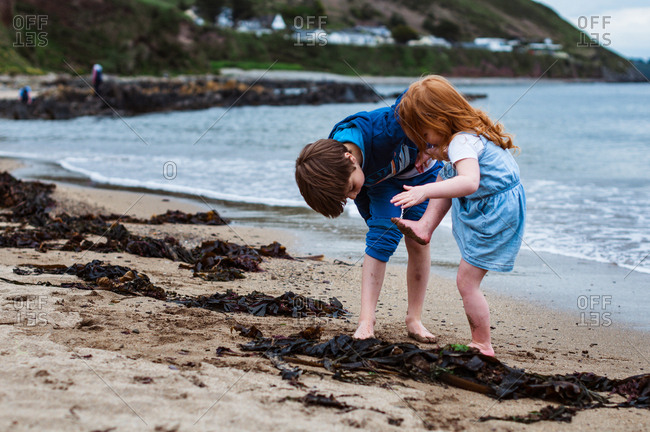 Boy and girl on the beach looking at dirty feet