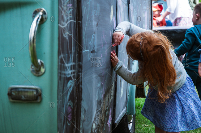 Girl drawing with chalk on a van at festival